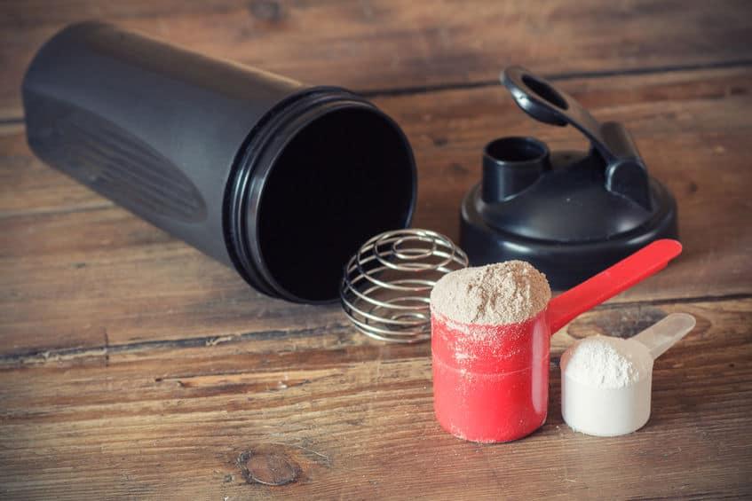 Proteína Whey con scoop y shaker.