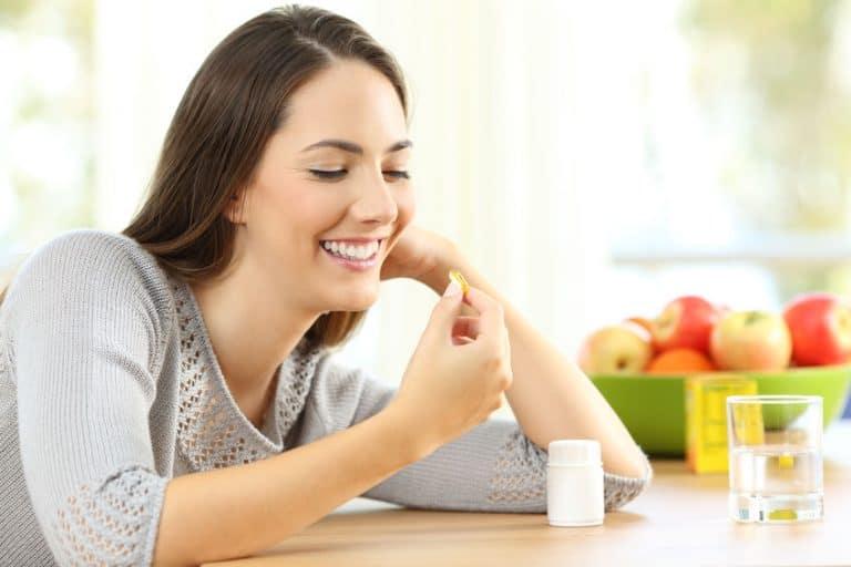 Mujer feliz tomando pastilla de gel