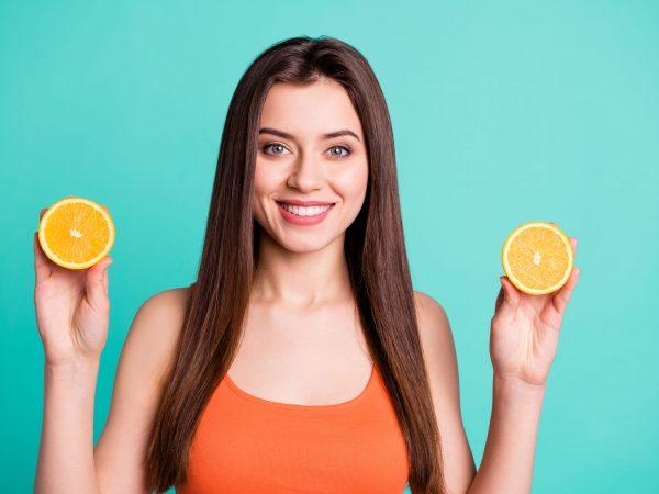 Mujer sosteniendo rodajas de naranja