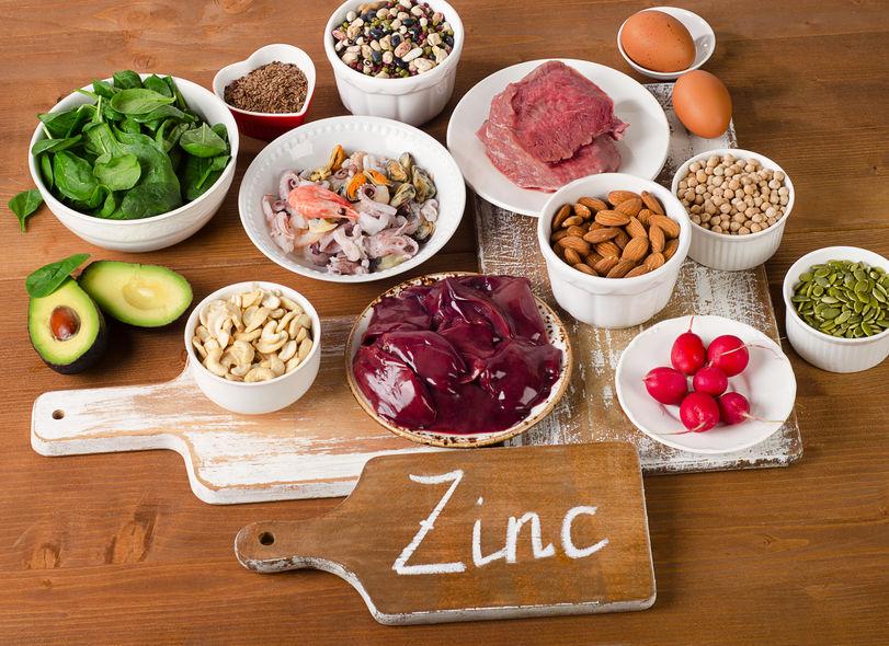 Alimentos con zinc mineral en una mesa de madera.