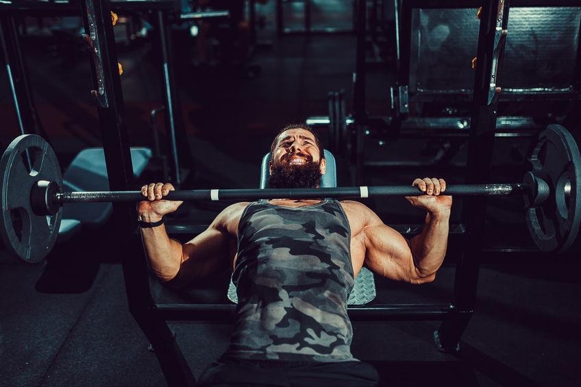 Apuesto joven haciendo ejercicios de press de banca en el gimnasio