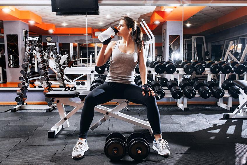Mujer bebiendo agua en gimnasio